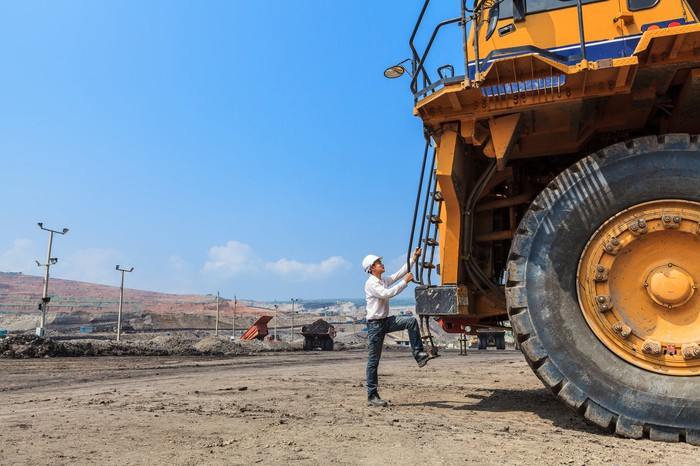 A worker climbs onto a large truck with a tire nearly double his size.