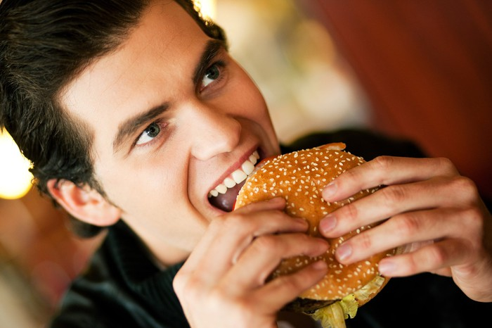 A man taking a bite out of a hamburger.
