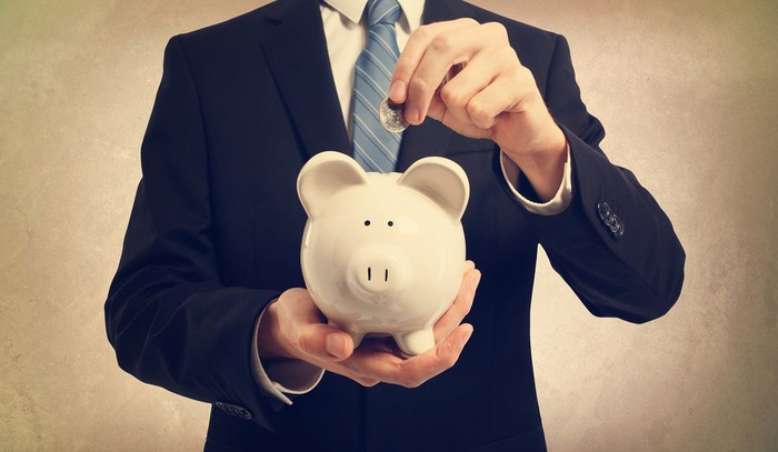 Man in suit placing coin in a piggy bank.
