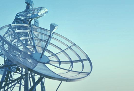 A satellite dish against a pale blue sky.