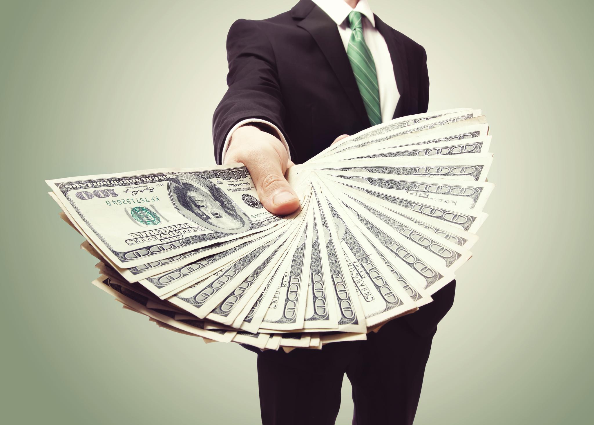 Man holding a handful of $100 bills.