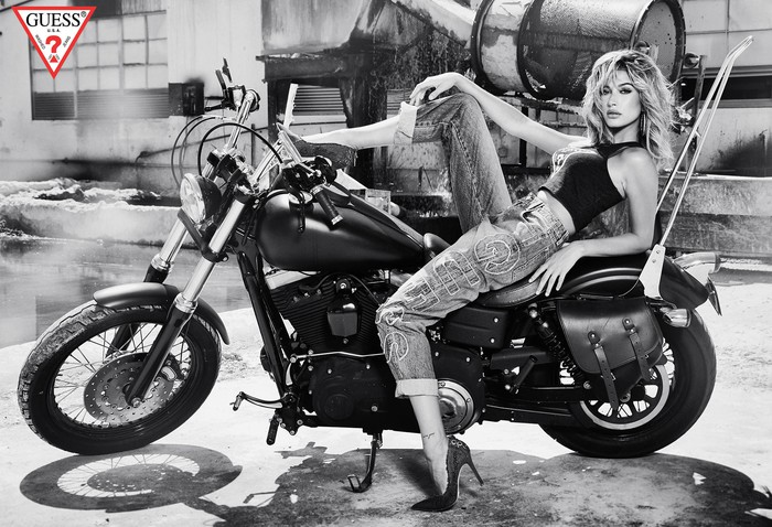 A woman sits on a motorcycle in trendy Guess brand jeans and high heels.