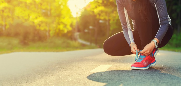 Woman tying her running shoes as the sun rises.