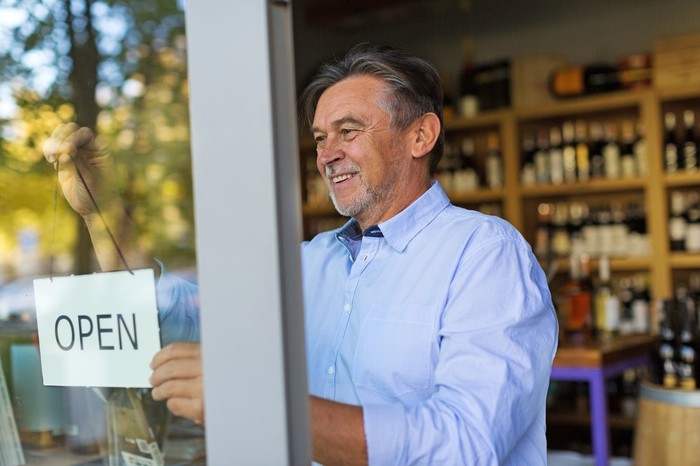 "Small business owner putting ""open"" sign on shop window."