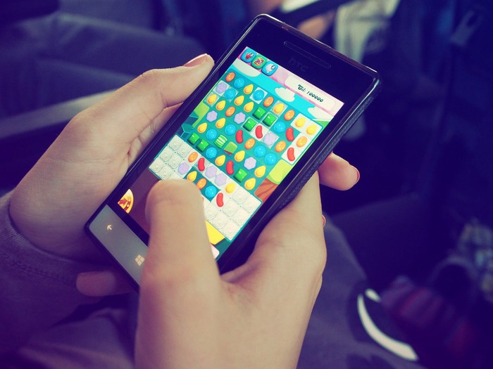 A person holding a smartphone and playing the mobile game Candy Crush.