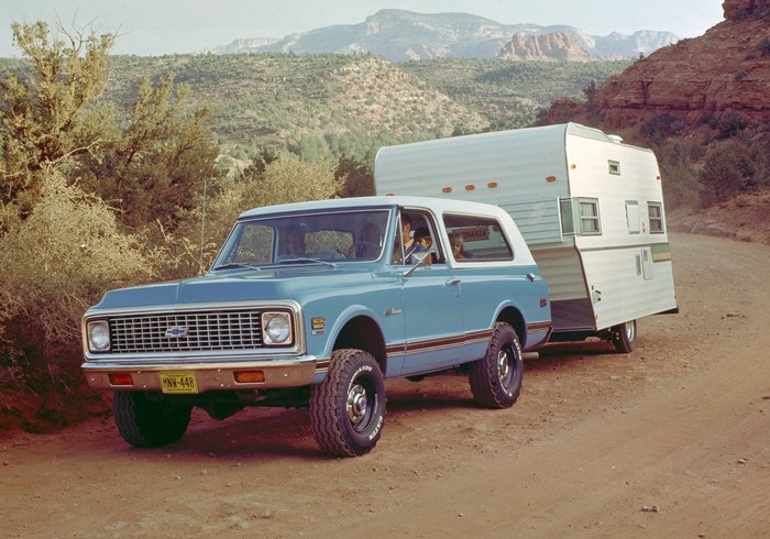 A blue 1969 Chevrolet K5 Blazer pulling a trailer on a dirt road.