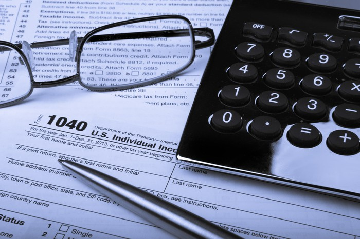 Tax form with glasses, pen, and calculator