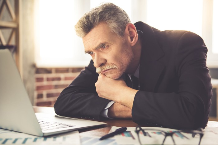 Tired businessman looking at his computer.