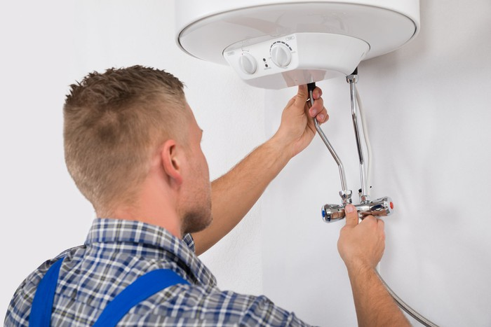 Worker fixing an electric boiler.