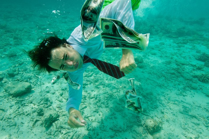 A businessman collecting money while swimming underwater, wearing formal clothes