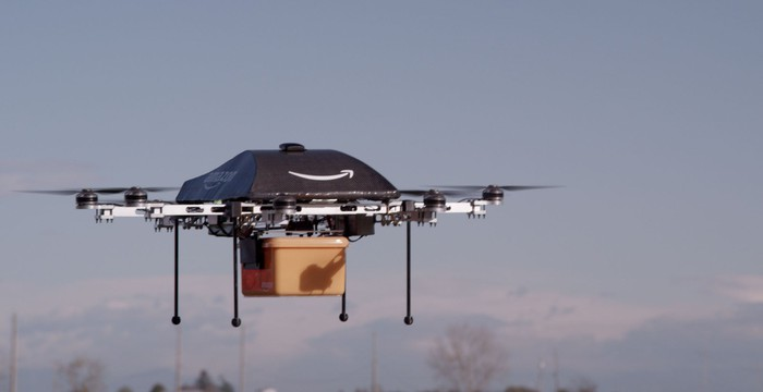 An Amazon package delivery drone flying while carrying a package.