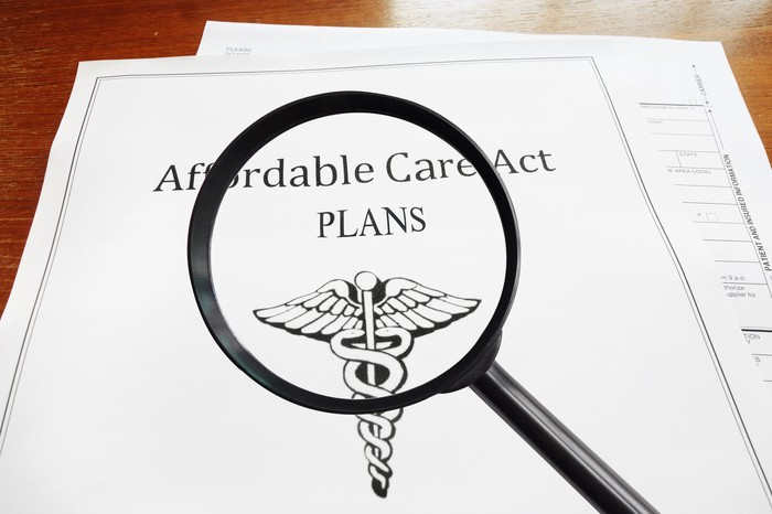 A magnifying glass lying on top of an Affordable Care Act policy.