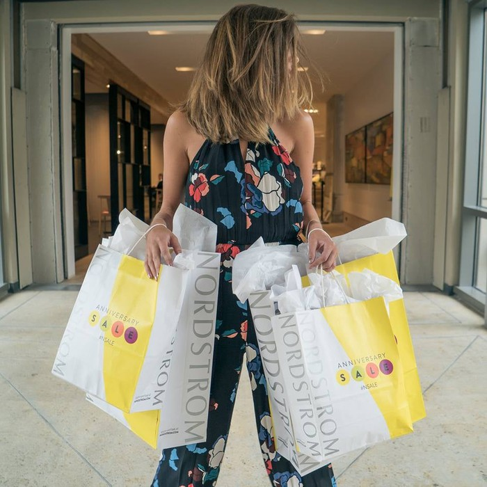 A woman holding multiple Nordstrom shopping bags.