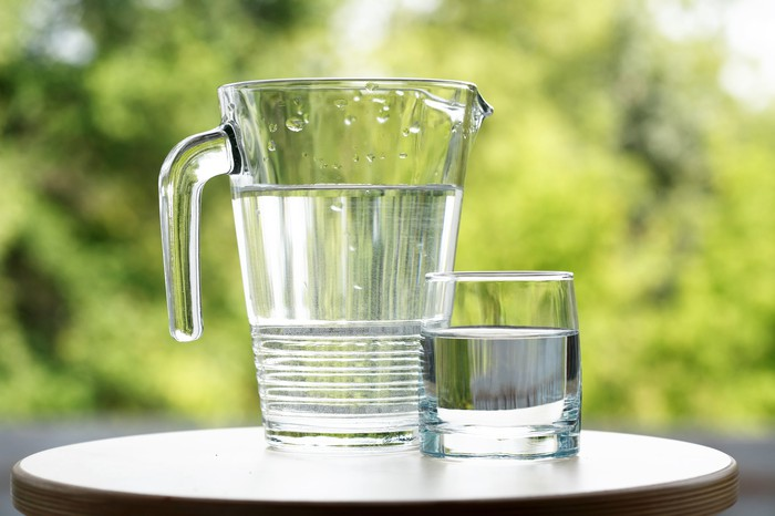 A water pitcher on a table with a glass of water beside it.