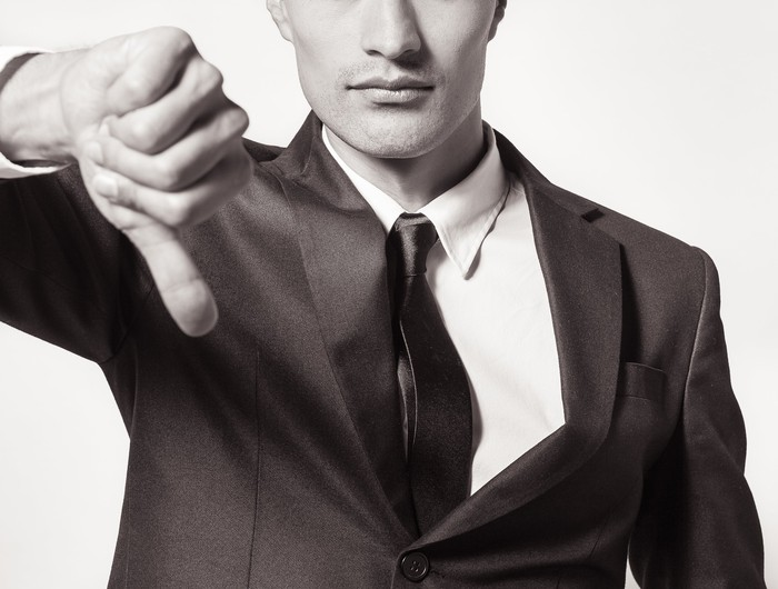 Man in suit giving thumbs down