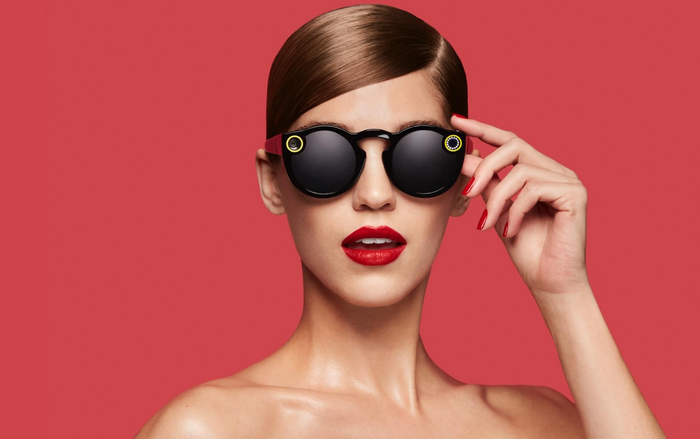 Model on red background wearing Snap Spectacles