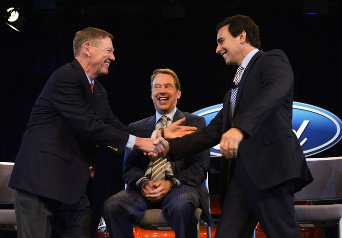 Alan Mulally shaking hands with Mark Fields during a press conference.