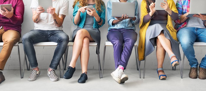 Seated people looking at laptops, tablets, and smartphones
