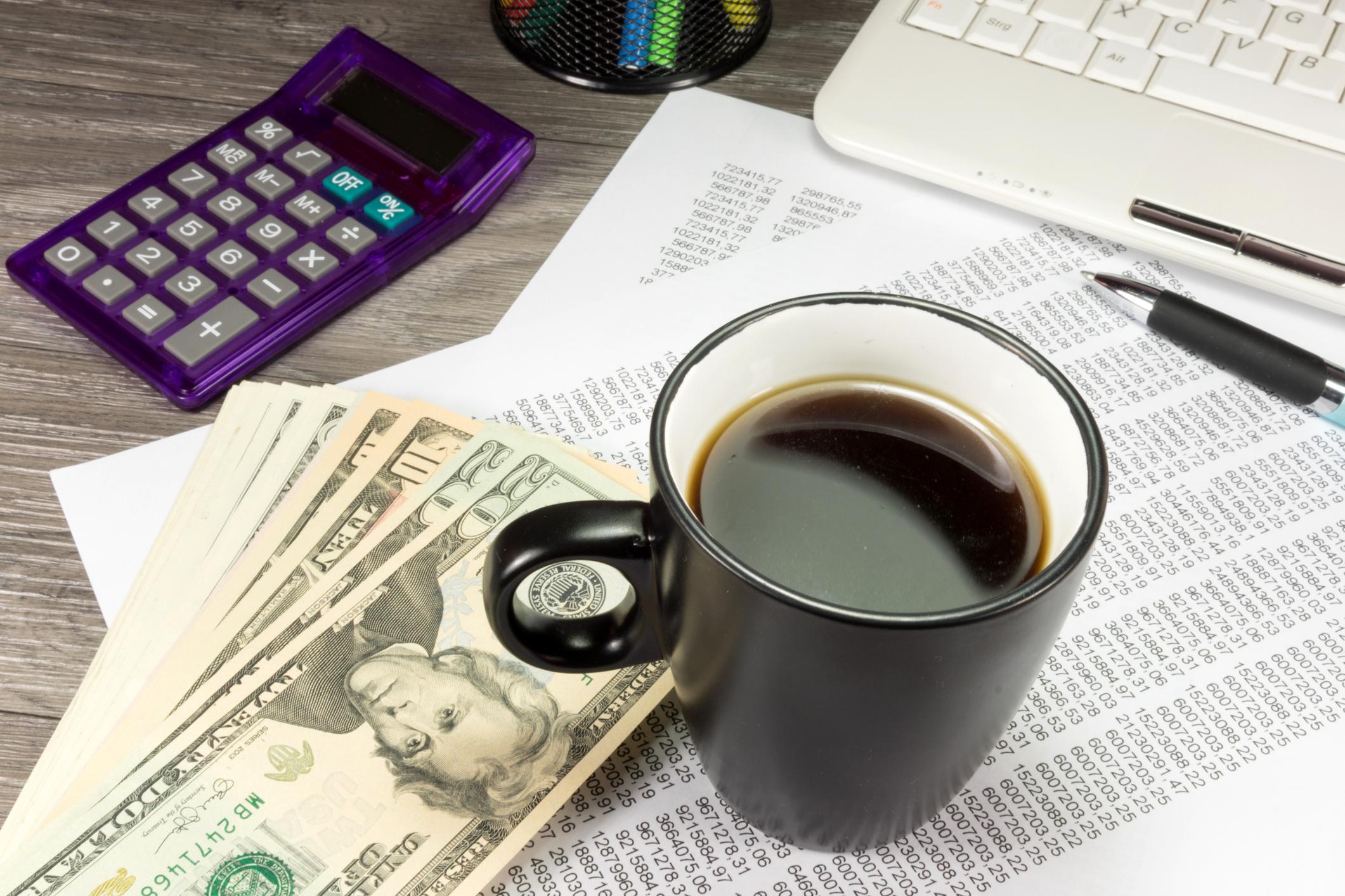 Calculator, cash, paperwork, and coffee