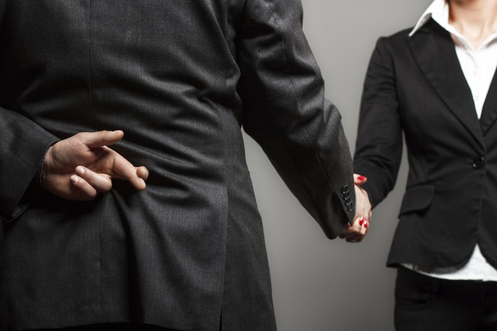 A man in a suit shakes a woman's hand while crossing his fingers behind his back.