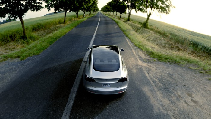 A silver Tesla Model 3 driving down a country road.