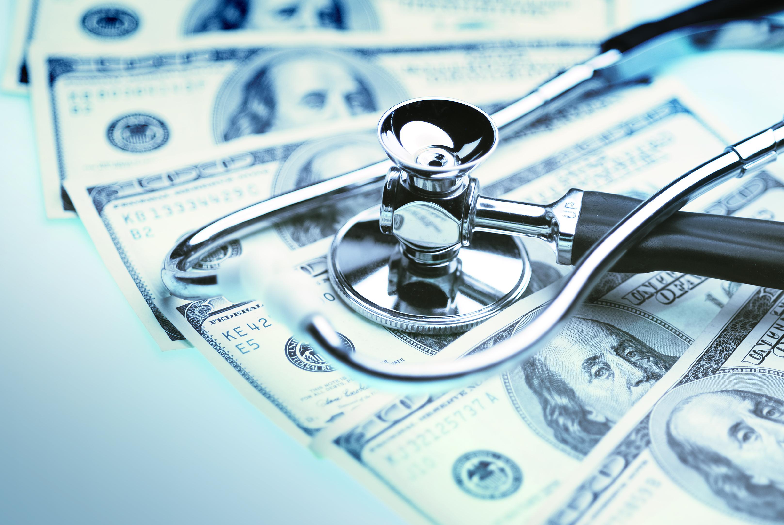 Stethoscope on hundred dollar bills