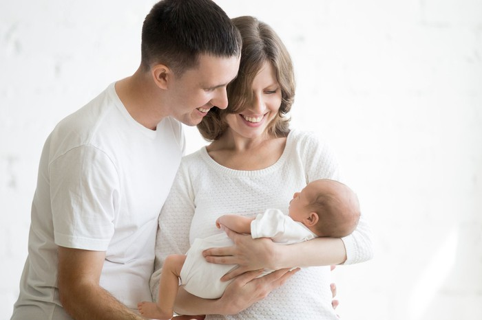 A couple look lovingly at their new baby.