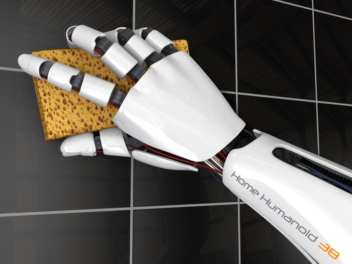 A robot cleans tile in a bathroom with a sponge.