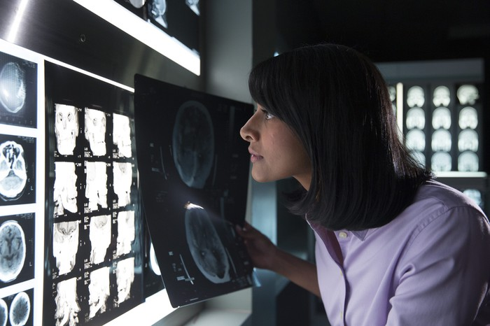 Woman viewing lighted panel of X-ray images