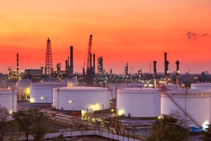 A landscape of a refinery with storage tanks.