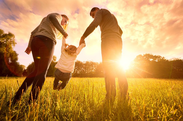 A man and a woman holding their child off the ground in a meadow at sunset.