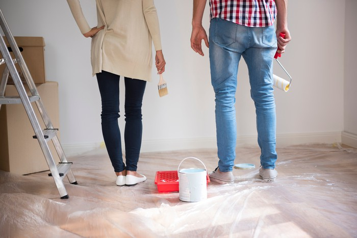 Couple standing in room considering paint colors