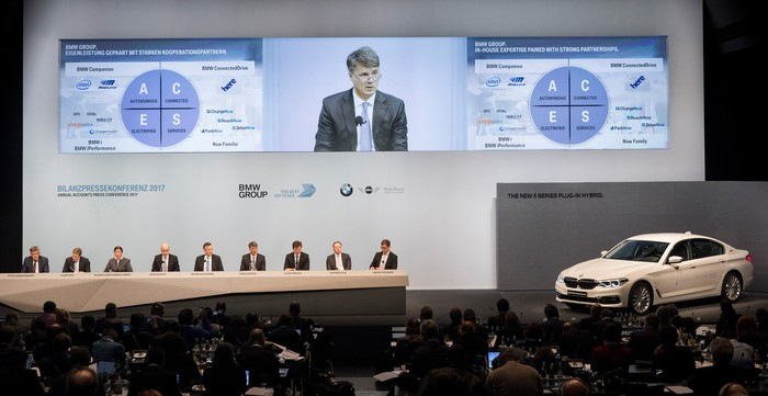 Several executives are seated on a big stage, along with a white BMW sedan. Video monitors above show a slide noting BMW's partnership with Intel and Mobileye.