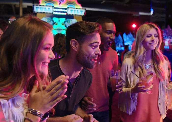 Four adults playing a video game at Dave & Buster's.