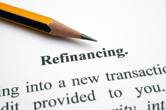 """Part of a paper is visible, on which is written """"refinancing,"""" Part of a pencil is shown, too."""
