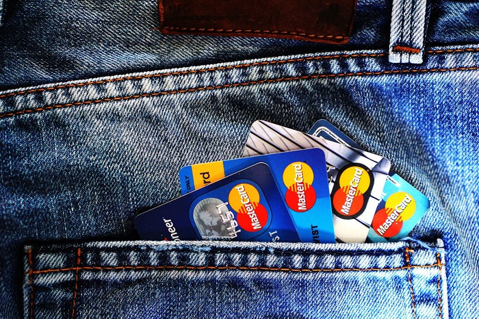 MasterCard brand credit cards sticking out of jeans pocket.