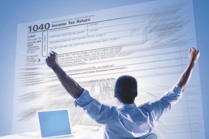 Man in front of projected image of tax return with hands raised in victory