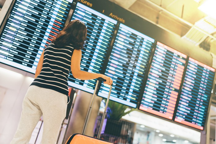 A woman looking at a large arrivals board at an airport.
