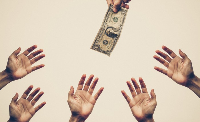 A hand holds a dollar bill just out of reach of other hands.