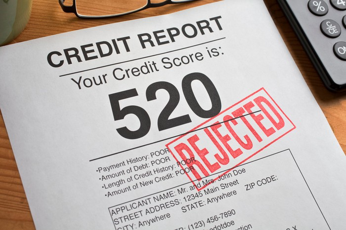 "A credit report with a 520 credit score stamped ""REJECTED."""