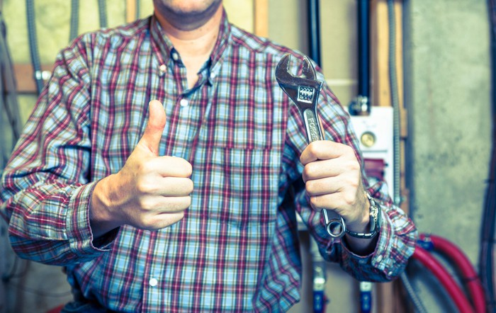 A handyman completes a project and gives a thumbs up.