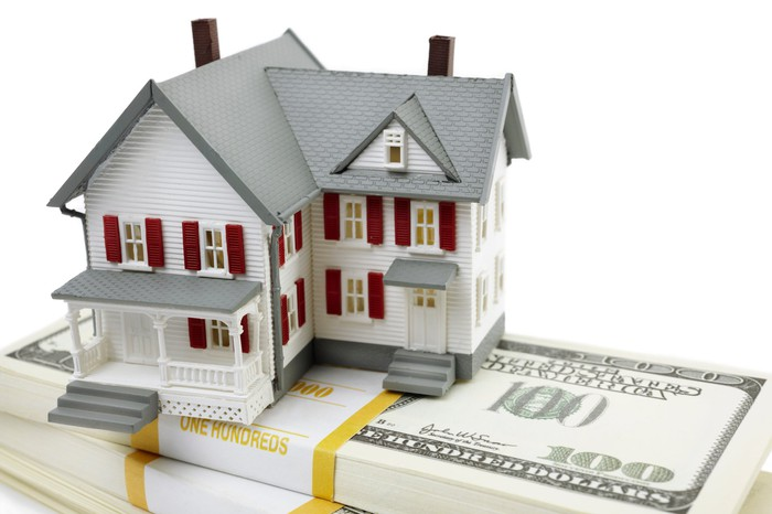 A house sits on top of a pile of money.