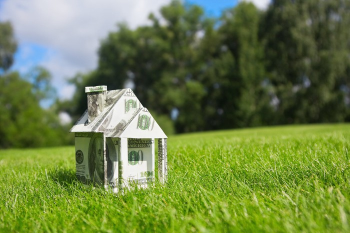 A small house made of money in a lush green field.