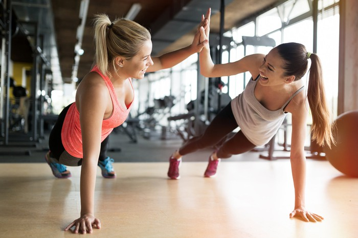 Two women in a gym give each other a high five as they do pushups.