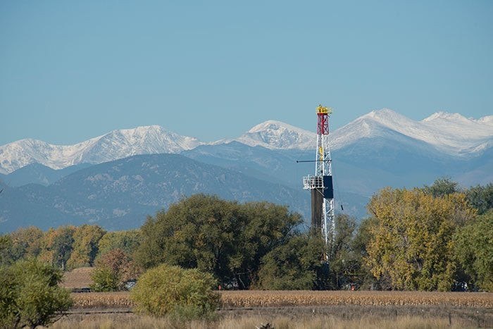 A drilling rig with mountains in the background.