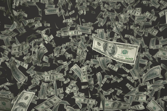 100 dollar bills falling from the sky.