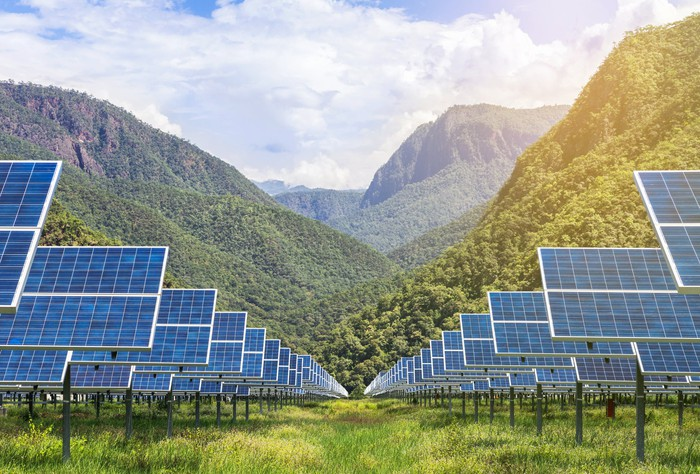 Two columns of solar panels stretching into green hills in the background.