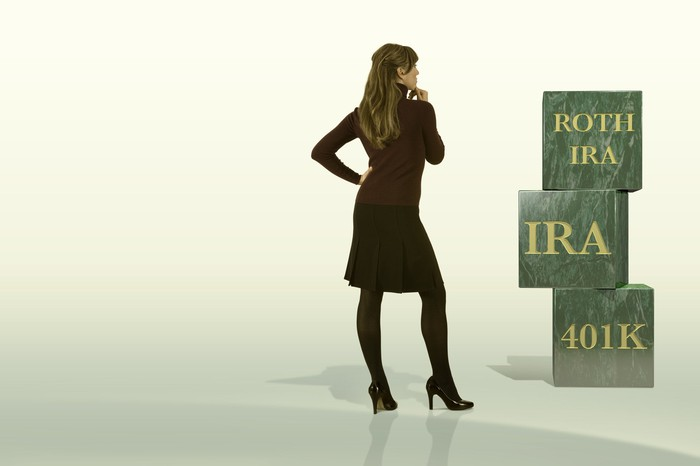 A woman looking at her retirement building blocks of Roth IRA, 401(k), and Traditional IRA.