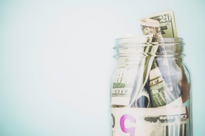 Jar of U.S. currency on blue background.
