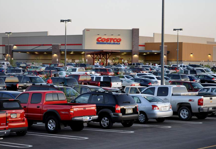 The exterior of a Costco store, as seen from a full parking lot.